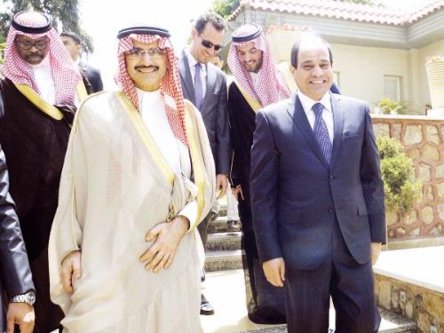 Egypt's ex-army chief and presidential candidate Abdel Fattah El-Sisi (R) walks alongside Prince Alwaleed Bin Talal, Chairman of Kingdom Holding Company, during a meeting in Cairo on Monday