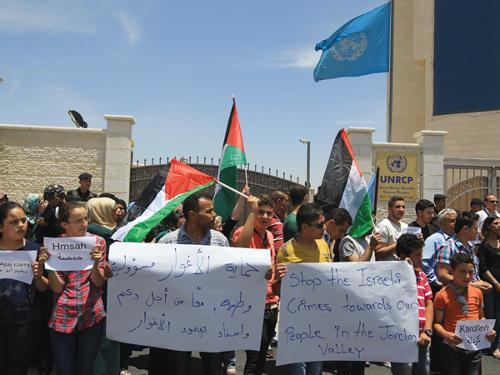 Palestinians demonstrate holding banners and waving national flags in front of the United Nations office demanding the world body's intervention against Israel's policies in the West Bank city of Ramallah.