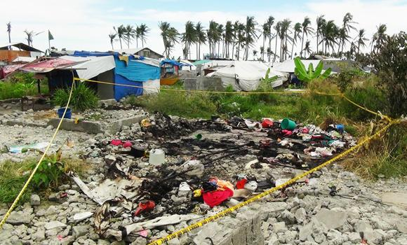 A police line is seen around the debris of a burned tent serving as temporary shelter for victims of Super Typhoon Haiyan in San Jose village, Tacloban City, on Wednesday. (AFP Photo/Marlon Tano)