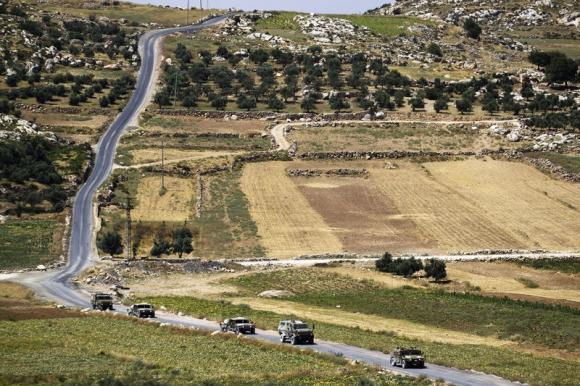 A convoy of Israeli military vehicles drives during an ongoing operation to locate three Israeli teens outside the West Bank City of Hebron.