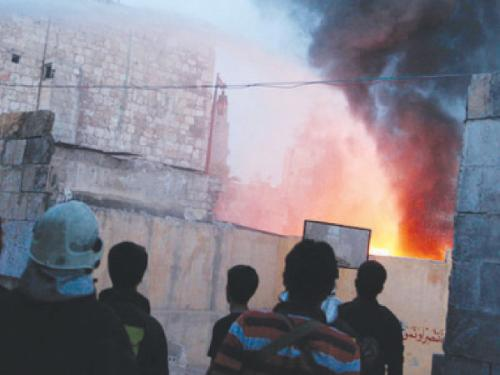 Firefighters put out a fire at a site hit by what activists said was a barrel bomb dropped by forces loyal to Syria's President Bashar Al-Assad in the old city of Aleppo
