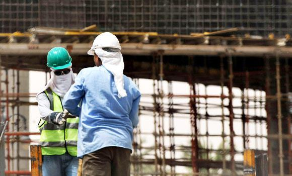 Asian workers work at a construction site in the Saudi capital Riyadh