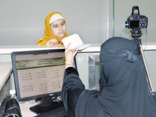A Saudi female officer processes a passenger's passport at King Abdulaziz International Airport (KAIA) on Monday after Jeddah Governor Prince Mishal Bin Majed opened the special immigration counters exclusively for women travelers at KAIA. The Passport Department has appointed as many as 74 Saudi women to work at the desks in a move to protect the privacy of female passengers.