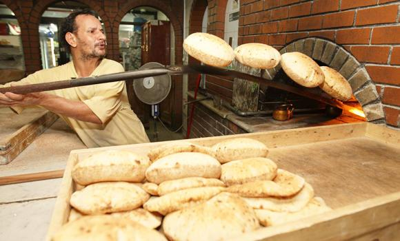 A baker removes bread from an oven.