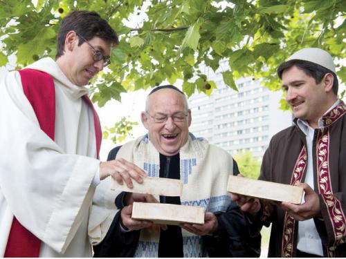 (From L) Pastor Gregor Hohberg, Rabbi Tovia Ben-Chorin and Imam Kadir Sanci hold bricks as they pose for photographers in the vacant lot where they hope to build a multi-faith prayer building, in Berlin