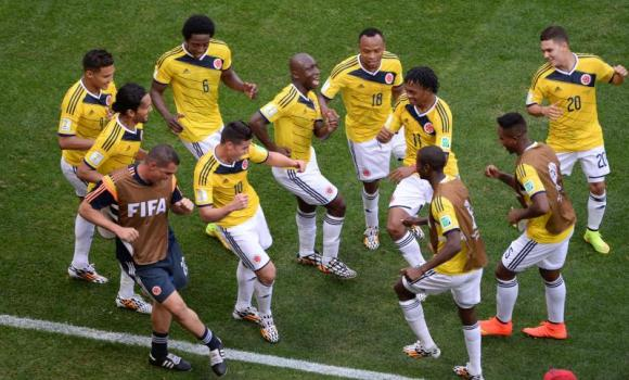 Colombian players dance after scoring against Ivory Coast at the Mane Garrincha National Stadium in Brasilia on Thursday