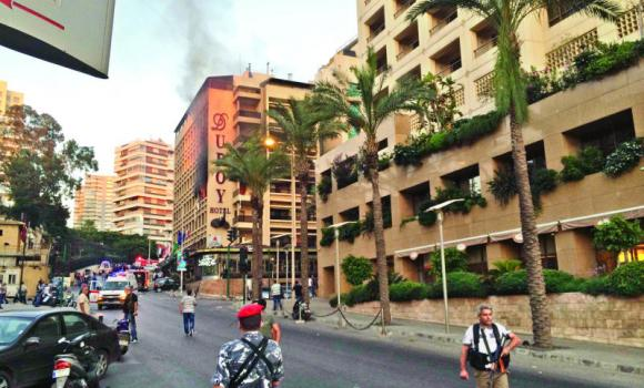 Policemen and security officials secure the area as smoke rises from Duroy hotel in Raouche, in western Beirut, on Wednesday.