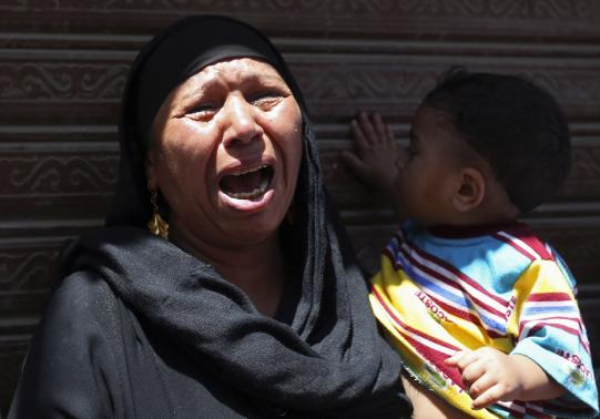 A woman carrying a child cries outside a court in Minya, south of Cairo, after the sentences of Muslim Brotherhood leader Mohamed Badie and his supporters were announced.