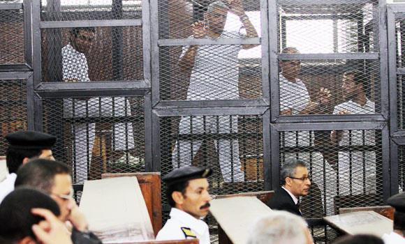 Al-Jazeera's acting bureau chief Mohammed Fahmy, a Canadian-Egyptian, center, and Australian correspondent Peter Greste, center right, appear in a defendant cage along with other defendants during a trial on terrorism charges in Cairo, Egypt, in this May 22, 2014 file photo. (AP)