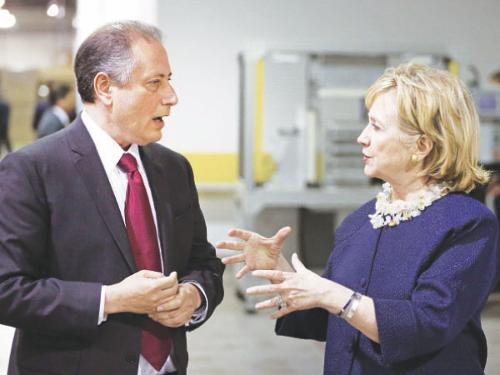 Hillary Clinton, right, talks with Intertech CEO Noel Ginsburg during a tour of Intertech Plastics in Denver on Sunday