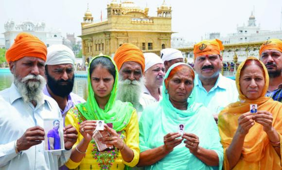 Relatives of Indian workers who were taken hostage in Iraq pose with photographs of their loved ones at the Golden Temple in Amritsar on Thursday.