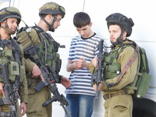 Israeli soldiers inspect the phone content of a Palestinian youth in the West Bank town of Hebron on Monday
