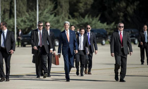 John Kerry walks with his bodyguards toward a plane at Jordan's Queen Alia International Airport in Amman.