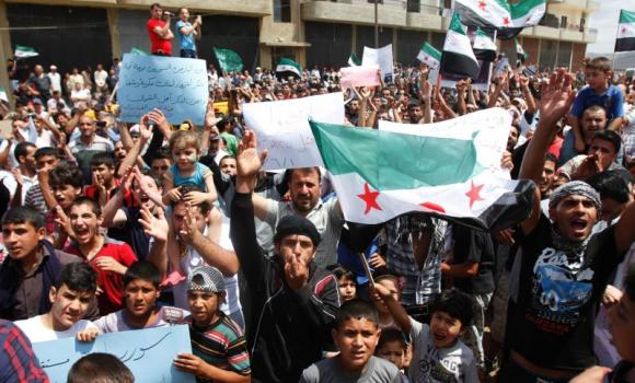 Syrian refugees carrying Free Syrian Army flags attend a protest against the election of Syrian President Bashar Assad in Tripoli, Lebanon, on June 1, 2014. (Reuters/Omar Ibrahim)