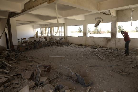 A teacher stands inside a damaged classroom after the building was bombed by a Libyan warplane at a university in Benghazi June 1, 2014.