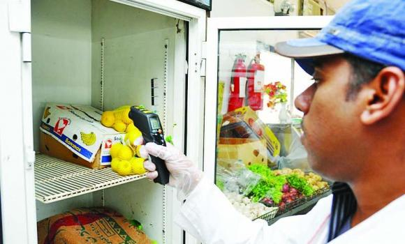 A Makkah Municipality official checks the temperature in which stored fruit is kept.
