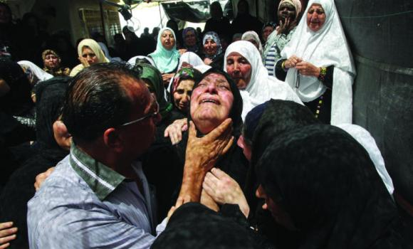 The mother of Mohammed Dudin, a 14-year-old Palestinian shot dead by Israeli troops in overnight clashes in Dura, weeps during his funeral in Hebron.