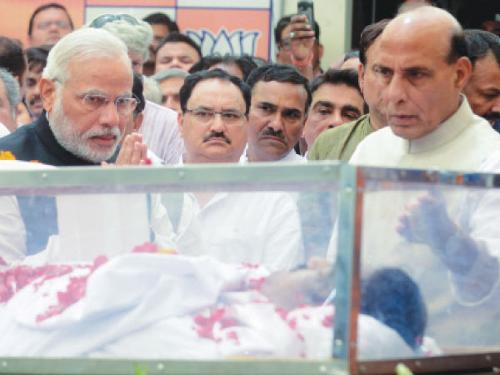 Indian Prime Minister Narendra Modi, left, pays his respects over the mortal remains of Gopinath Munde, India's Rural Development and Water and Sanitation Minister, as BJP President Rajnath Singh, right, looks on at the Bharatiya Janata Party (BJP) headquarters in New Delhi on Monday. — AFP