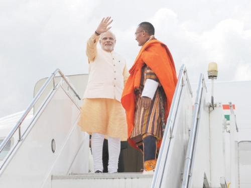 India's Prime Minister Narendra Modi (L) waves next to his Bhutanese counterpart Tshering Tobgay before Modi's departure at the airport at Paro in Bhutan on Monday.
