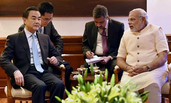 Chinese Foreign Minister Wang Yi, left, sits with Indian Prime Minister Narendra Modi.