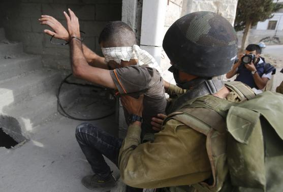 An Israeli soldier detains a Palestinian during an operation to locate three Israeli teens near the West Bank City of Hebron June 21, 2014.