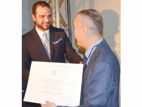 "Consul General Simone Petroni awards Italian businessman Fermo Maria Giuseppe Grigis with the ""Ordine della Stella d'Italia,"" or ""Order of the Star of Italy"", for his contribution to the commercial relations between Italy and the Kingdom."