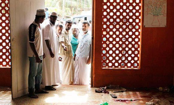Sri Lankan Muslims look at the blood stained floor where a mob attacked and killed three Muslims, in Aluthgama, 50 kilometers south of Colombo, Sri Lanka