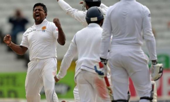 Sri Lanka's Rangana Herath, LEFT, celebrates dismissing England's Chris Jordan on the fifth day of the second Test cricket match between England and Sri Lanka at Headingley in Leeds, northern England, on Tuesday.
