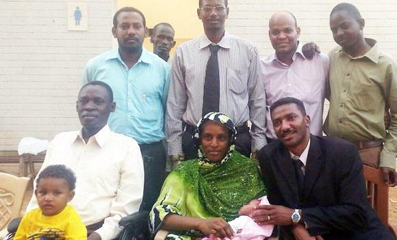 In a handout picture obtained from the legal team and taken with a smart phone, Meriam Yahia Ibrahim Ishag (seated C), a Christian Sudanese woman sentenced to hang for apostasy last month, poses for a picture with her husband Daniel Wani, a US citizen originally from South Sudan (L), her newborn baby and the couple's 20-month-old son, one of her lawyers Mohanad Mustafa (R), and other members of the legal team at an undisclosed location in Khartoum on Monday.