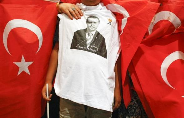 Turk expatriates hold their national flag at a political rally for Turkey's Prime Minister Tayyip Erdogan in Chassieu, near Lyon.