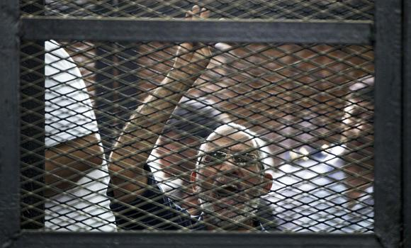 A file picture taken on June 7, 2014 shows Egyptian Muslim Brotherhood leader Mohamed Badie gesturing as he shouts from inside the defendants cage during his trial in Cairo.