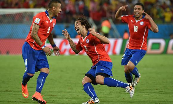 Chile's forward Jorge Valdivia (C) celebrates with Chile's midfielder Arturo Vidal (L) after scoring during a Group B football match between Chile and Australia at the Pantanal Arena in Cuiaba during the 2014 FIFA World Cup on Friday.