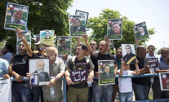 Palestinian activists hold placards during a protest outside the Israeli run Ayalon prison in Ramle, near Tel Aviv, calling for the release of Palestinian prisoners, on May 23, 2014, as they express solidarity with Palestinian prisoners who are on hunger strike. (AFP Photo/ Ahmad Gharabli)