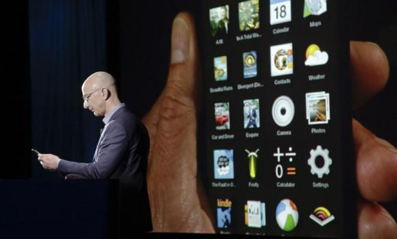 Amazon CEO Jeff Bezos shows off the 3D features of his company's new Fire smartphone at a news conference in Seattle, Washington, on Wednesday.