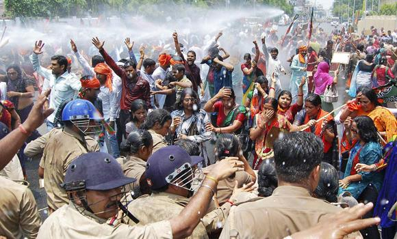 Activists protesting against official tolerance for sexual violence against women get an untimely bath from police, who fired water cannons to stop them from moving toward the office of Akhilesh Yadav, the chief minister of the northern Indian state of Uttar Pradesh, in the city of Lucknow on Monday. (Reuters/Pawan Kumar)