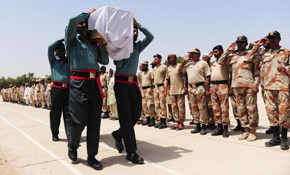 Pakistani Rangers carry the coffin of a colleague killed during an assault by militants on Karachi airport during funeral ceremonies in Karachi on Monday.