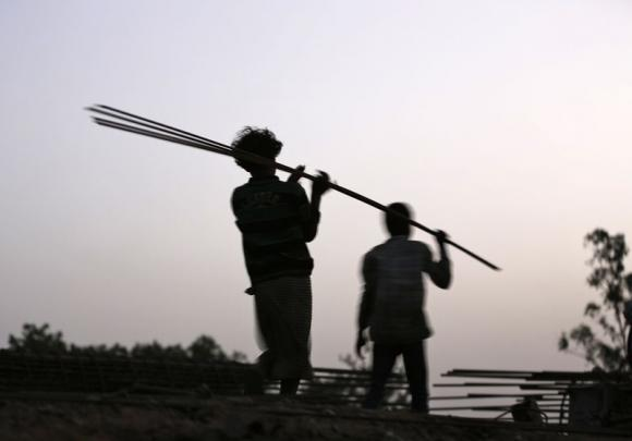 Laborers carry iron rods at the construction site of a flyover on the outskirts of Ahmedabad.