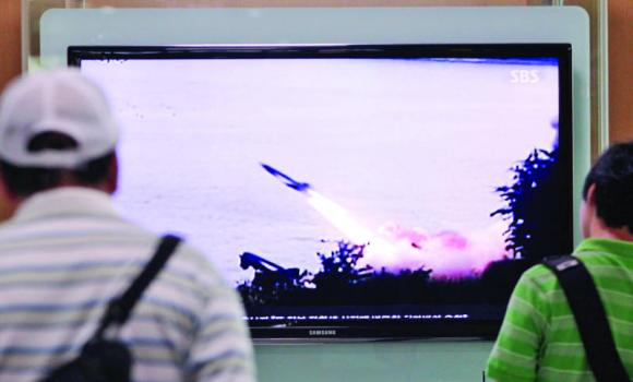 People watch a TV news program showing the missile launch conducted by North Korea, at Seoul Railway Station in Seoul, South Korea.