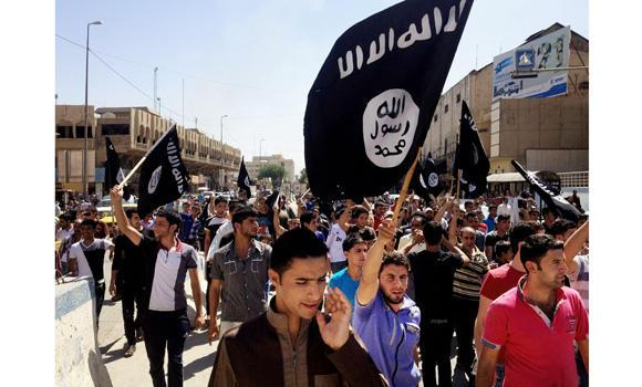 Demonstrators carry flags of the Islamic State of Iraq and the Levant (ISIL) during a rally in front of the provincial government headquarters in Mosul, 360 kilometers northwest of Baghdad, on June 16, 2014. Suspected ISIL militants have kidnapped 40 Indian construction workers in Mosul on Wednesday.