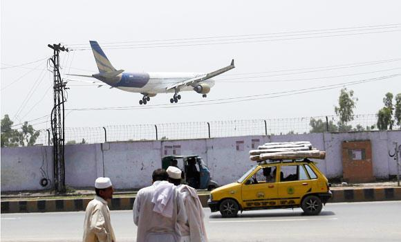 A Shaheen airplane is about to land at Bacha Khan airport in Peshaswar on Thursday. One woman was killed and three crew members were wounded as gunmen shot an Airbus 310 plane carrying 178 passengers from Saudi Arabia as it landed in the northern Pakistani city of Peshawar.