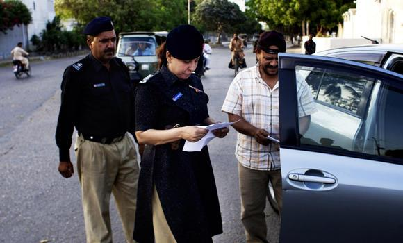 In this Monday, May 5, 2014 photo, Pakistani female police officer Syeda Ghazala checks documents of a vehicle in Karachi, Pakistan. Just days into her job running a police station in Pakistan's largest city, Syeda Ghazala had to put her training to the test: she opened fire with her .22-caliber pistol at a man who shot at police when they tried to pull him over during a routine traffic stop.