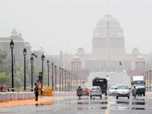 Commuters travel through a mirage on a hot summer day in front of India's presidential palace Rashtrapati Bhavan in New Delhi on Saturday. Temperature in New Delhi on Saturday reached 45 degrees Celsius (113 degrees Fahrenheit), according to information posted on India's metrological department website.