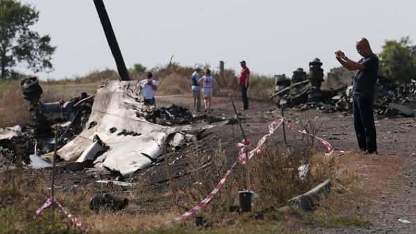 A Malaysian air crash investigator (R) works at a crash site of the Malaysia Airlines Flight MH17 near the village of Hrabove (Grabovo), Donetsk region July 24, 2014.
