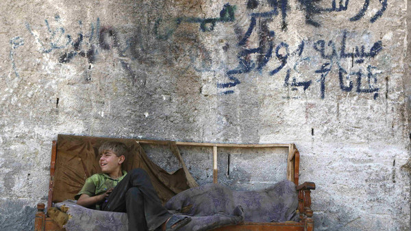 A boy sits on a sofa along a street in the Al-Fardous neighbourhood of Aleppo July 15, 2014.