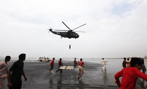 Rescue workers in red shirts carry a stretcher as they run to receive the body of a victim who had drowned on Wednesday, from a Pakistan Navy helicopter, after search rescue operation by the navy at Karachi's Clifton beach on Thursday.