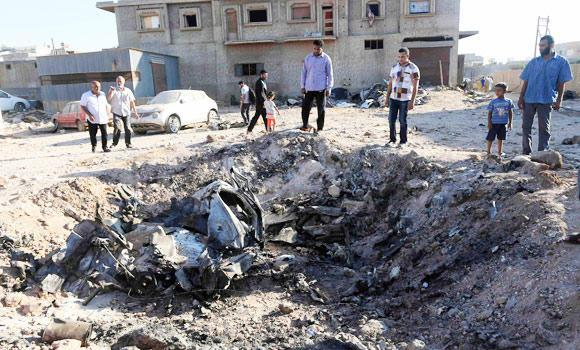 People look at the wreckage of a government MiG warplane which crashed during Tuesday's fighting, in Benghazi, in this July 29, 2014 photo.