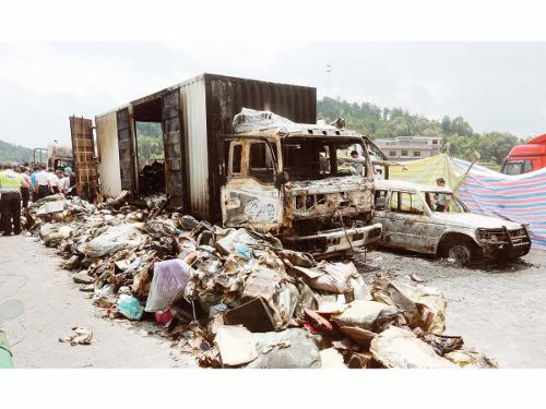Debris is seen next to burnt vehicles after an explosion and a fire following a traffic accident, at a section of the Hukun (Shanghai to Kunming) highway in Shaoyang, Hunan province, on Saturday.