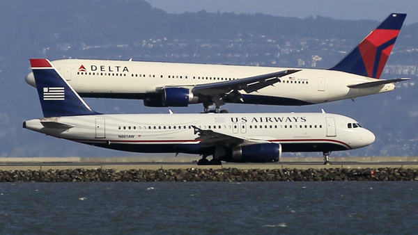 A Delta plane lands as a U.S. Airways plane waits to take off at San Francisco airport, California.