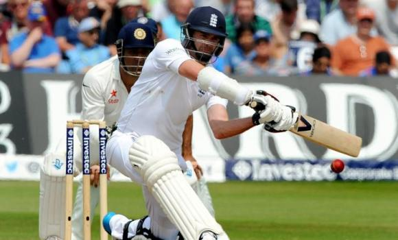 England's James Anderson plays a shot watched by India's wicket keeper M. S. Dhoni during day four of the first Test between England and India at Trent Bridge cricket ground, Nottingham, England, Saturday.