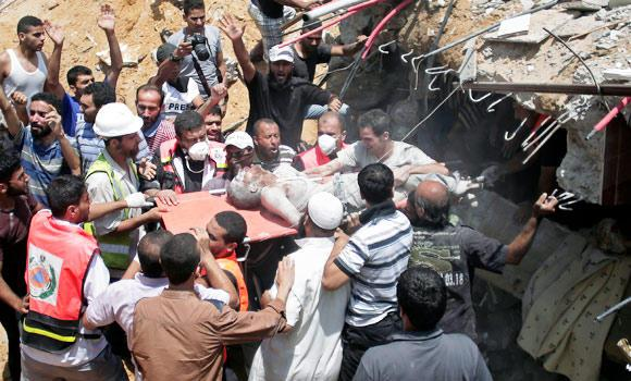 Palestinian rescue workers and civilians remove a lifeless body from the rubble of a house destroyed by an Israeli missile strike, in Gaza City, on Monday.